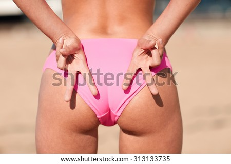 summer, sport, gesture, holidays and people concept - close up of woman buttocks and hands showing beach volleyball hand sign meaning angle attack block - stock photo