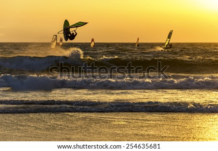 Summer sports: windsurfer speeding fast against the sunset - stock photo