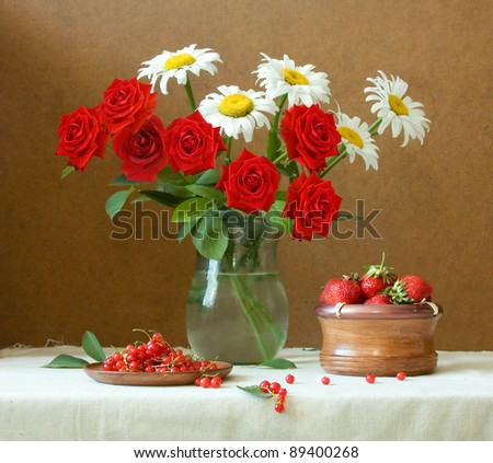 Summer still life huge bunch of with red velvet roses and chamomile flowers, strawberries and currants - stock photo
