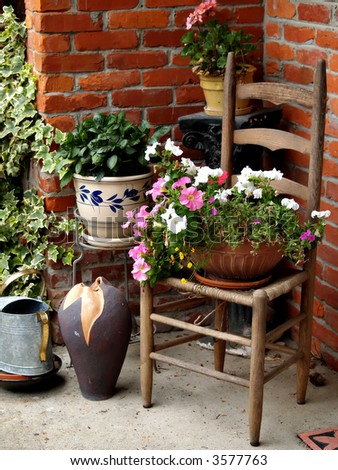 Summer still life of a wicker chair, pots of flowers, watering can, and a vase against a brick wall - stock photo