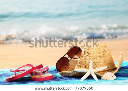 Summer straw hat with towel,sunglasses and flip flops on sandy beach - stock photo