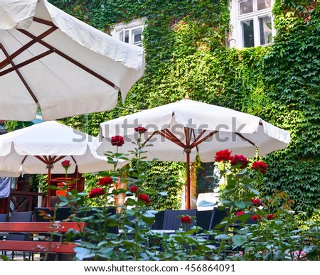 summer street cafe interior in green leaves, ornate with flowers and decorative elements, white umbrella - stock photo