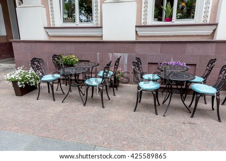 Summer street cafe. Openwork tables of street cafes in the summer waiting for visitors. Cozy old coffee shop bistro on the street summer town