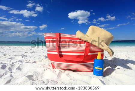 Summer sun protection at the beach, Beach sun hat and sunscreen on the sand at  beautiful beach.  Logos removed - stock photo