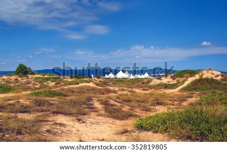 Summer sunny day. Blue sky and dry plants on the sand. White tents and mountains in the background. Black Sea coast. - stock photo