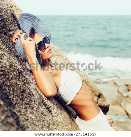 Summer sunny fashion portrait of pretty young sensual woman posing on the rocks alone on the ocean seashore. Outdoors lifestyle portrait