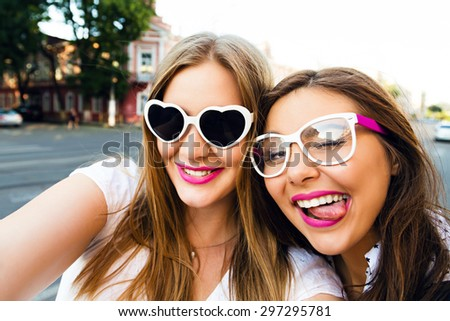 Summer sunny image of two sisters best friends brunette and blonde girls having fun on the street, making selfie,wearing funny vintage sunglasses, bright stylish make up long hairs. - stock photo