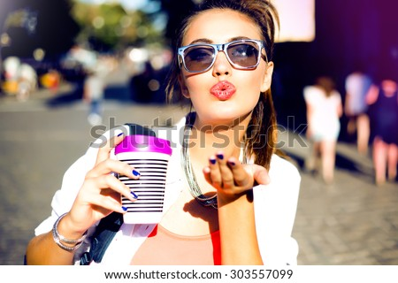 Summer sunny lifestyle fashion portrait of young stylish hipster women walking on street,wearing cute trendy outfit,drinking hot latte,smiling enjoy weekends,travel with backpack,coffee,rest,lounge  - stock photo