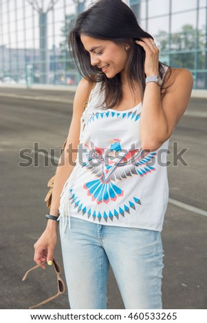 Summer sunny lifestyle portrait of young happy woman walking on the street with backpack