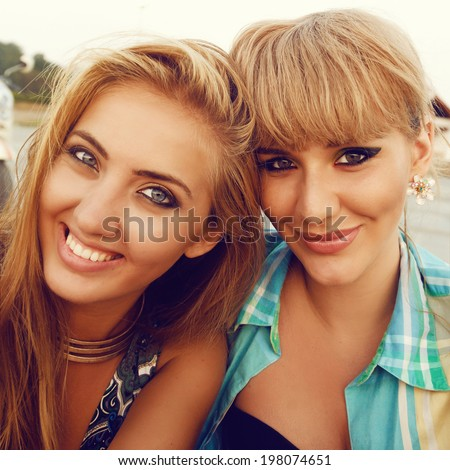 Summer sunny portrait of two young pretty blondes, smiling and having fun. Fring selfie and enjoy their friendship and free time holidays. - stock photo