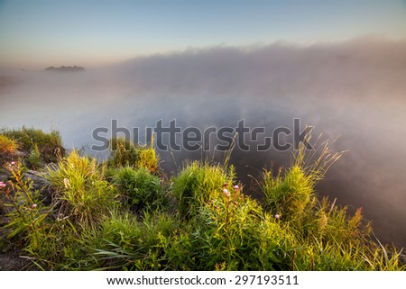 summer sunrise over the river with a fog. - stock photo
