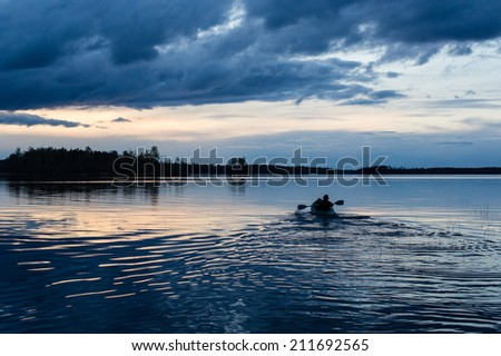 Summer sunset kayaking at Vuoksa lake - stock photo