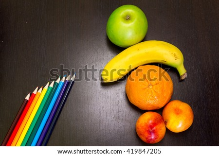 Summer tasty fruits on a dark background next to colored pencils