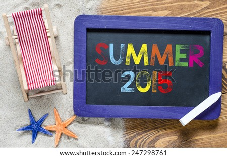 Summer 2015 text. Summer 2015 text with lounge and starfishes, blackboard and sand - stock photo