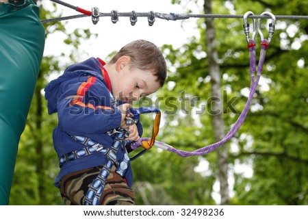 Summer time. Young boy climbing in the forest. - stock photo