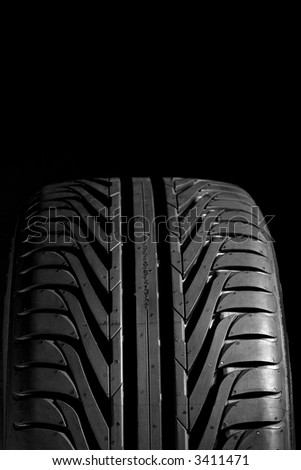 Summer tire (225/45R17), isolated on black. Frontal view with copyspace above. - stock photo