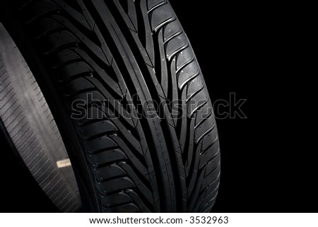 Summer tire (225/45R17) on black background. It's a new one. - stock photo