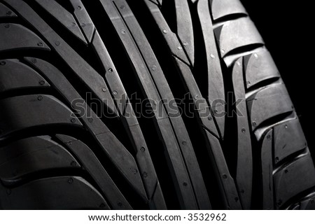 Summer tire (225/45R17) on black background. It's a new one. Close-Up. - stock photo