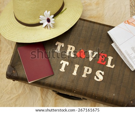 "Summer travel hat,flower,old suitcase,brown passport,map and wooden letters: ""travel tips"" - stock photo"