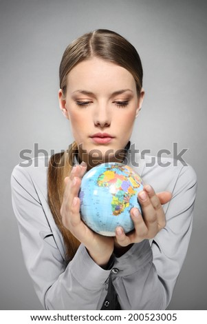Summer travel plan.  A woman holding a globe in his hands