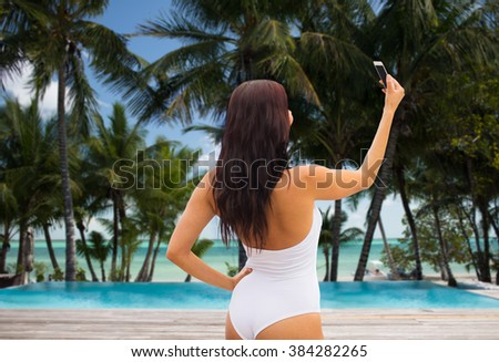 summer, travel, tourism, technology and people concept - sexy young woman taking selfie with smartphone over resort beach with palms and swimming pool background