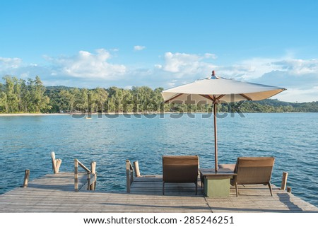 Summer, Travel, Vacation and Holiday concept - Beach chairs and umbrella on wooden desk against blue sky in Phuket,Thailand - stock photo