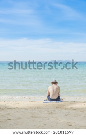 Summer, Travel, Vacation and Holiday concept - Man sitting on beach in Phuket,Thailand