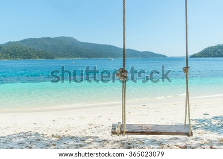 Summer, Travel, Vacation and Holiday concept - Swing hang from coconut palm tree over beach sea in Phuket ,Thailand. - stock photo