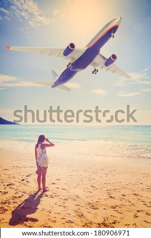 summer travel. young woman is standing on beach with aeroplane flying above - stock photo