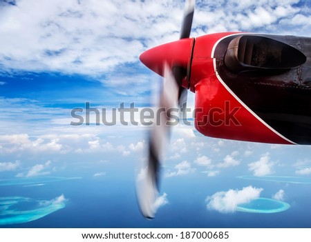 Summer traveling concept, small plane flying to the beach resort, scene destination, luxury aerial transport, tourism to exotic country - stock photo