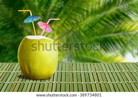 Summer tropical cocktail in fresh green coconut with two colorful umbrellas on palm tree leaves background - stock photo