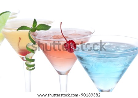 Summer Tropical Martini Cocktails with vodka, apple and peach liqueur, pineapple and cranberry juice, lime, lemon, blue curacao, maraschino cherry, and orchid isolated on a white background - stock photo