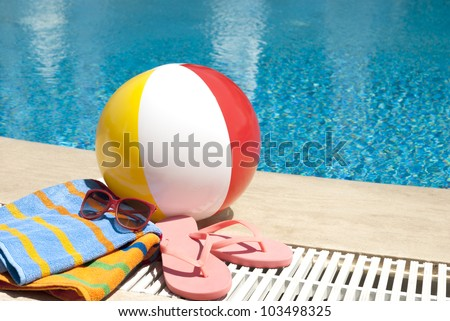 Summer vacation accessories  by the swimming pool - stock photo