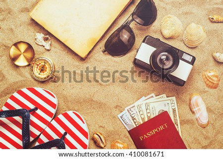 Summer vacation accessories on tropical sandy ocean beach, holidays abroad - summertime lifestyle objects and US American dollars in flat lay top view arrangement - stock photo