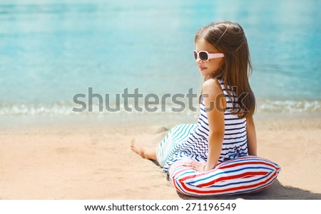 Summer, vacation and people concept - little girl resting on the sand beach near sea in sunny day - stock photo