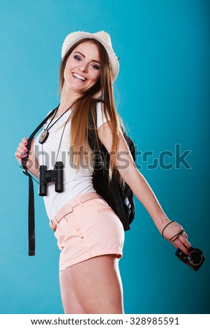 Summer vacation and tourism concept. Smiling woman in straw hat with backpack binocular camera in hand on blue