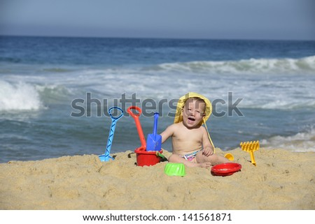 Summer vacation: Baby playing with beach toys in the sand - stock photo
