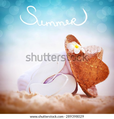 Summer vacation background, still life of of beach items with text Summer over it, white flip flops with straw hat  towel on sandy coast, summertime relaxation and holidays  - stock photo