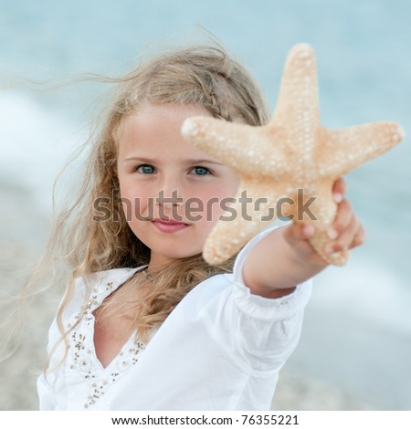 Summer vacation - beautiful girl with starfish at the beach