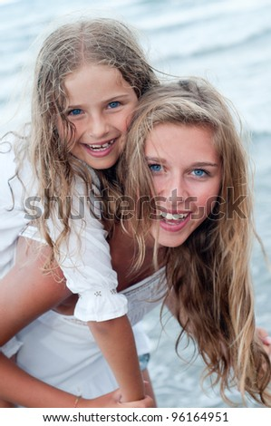 Summer vacation - Beautiful girls playing on the beach - stock photo