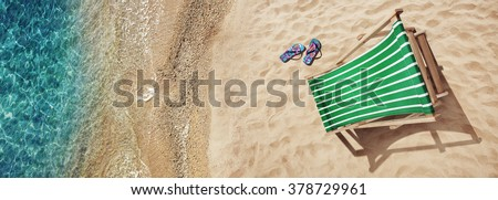 Summer vacation. Blue sandals by seashore. Blue sea surface with waves, texture water. Flat mock up for design. - stock photo