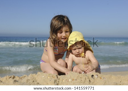 Summer vacation: Children playing in the sand on the beach - stock photo