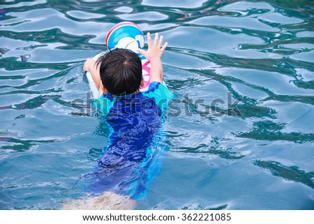 Summer vacation concept - Back view of asian boy with kick board and ball in pool. Outdoor. Swimming is very good exercise for good health. - stock photo