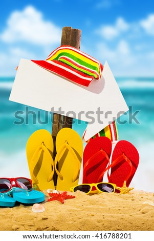Summer vacation concept--Color Flipflops on a sandy ocean beach with arrow sign