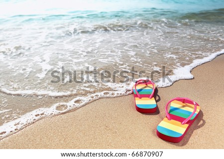 Summer vacation concept--Flipflops on a sandy ocean beach - stock photo