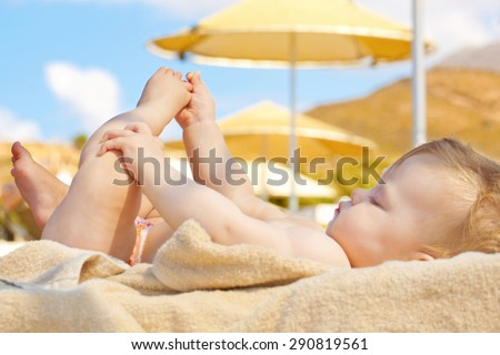 Summer vacation concept. Happy baby on the beach. - stock photo