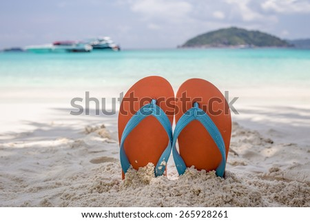 Summer vacation concept--Orange flip-flop on the white sand beach - stock photo