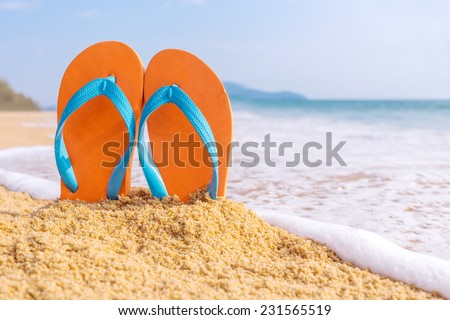 Summer vacation concept--Orange Flipflops on a sandy ocean beach - stock photo