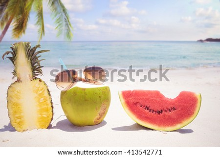 Summer vacation concept with sunglasses and fruit on sandy tropical beach  - stock photo