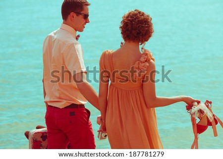 Summer vacation concept. Young happy married hipsters in trendy eyewear and clothes walking, talking and holding their shoes. Sunny summer day. Copy-space. Outdoor shot  - stock photo